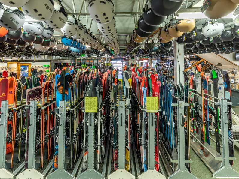 Rows of rental skis and helmets inside of Ski Haus.