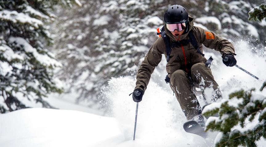 skiing the trees in deep powder on Salomon alpine skis