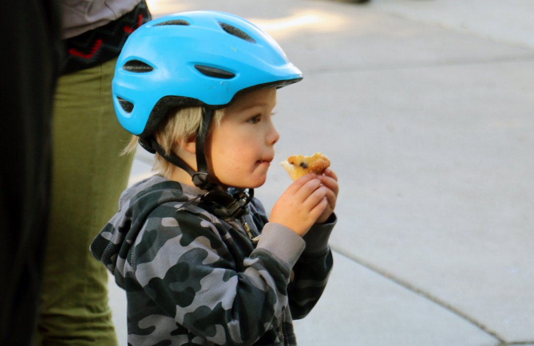 A young bike commuter enjoys the the Ski Haus Free Pancake Breakfast for Colorado Bike to Work Day