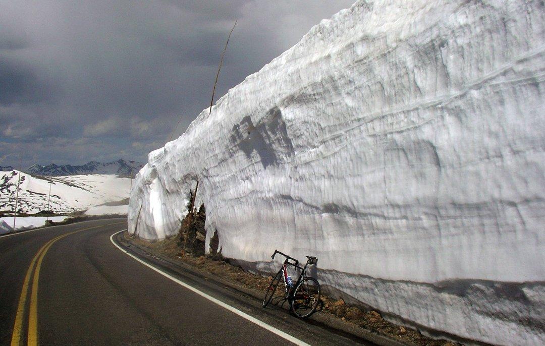 A road bike leaning against a massive snow drift on Trail Ridge Road RMNP