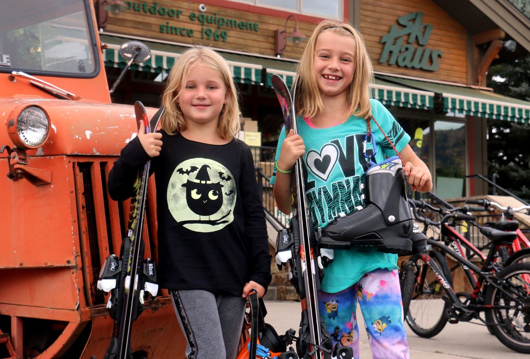two happy kids pick up their season rental skis at ski haus steamboat springs colorado